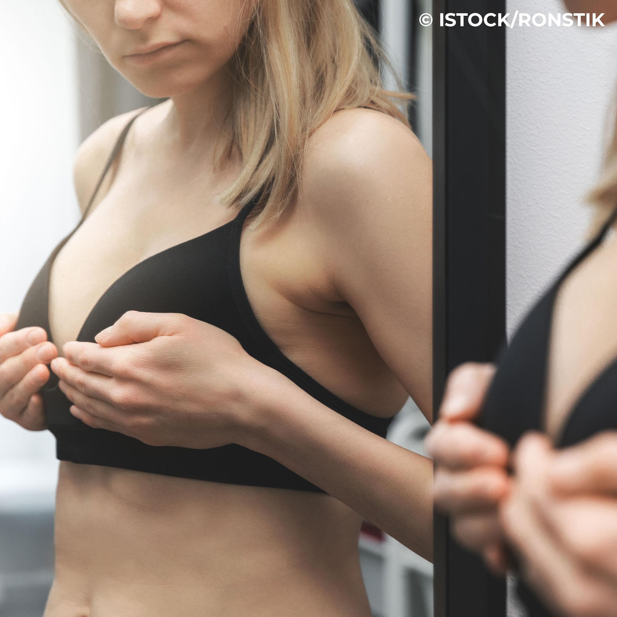 Frau betrachtet ihre Brust kritisch im Spiegel